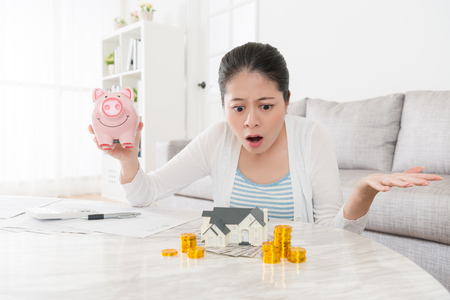 young pretty housewife holding piggy bank sitting in living room and looking at house model feeling dumbfounded because her deposit not enough buying new apartment.