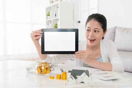 陽気なかなり主婦の家族のための新しい家を購入し、デジタル タブレット パッド白空白画面を表示を保有を計画します。