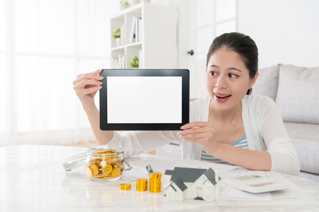 cheerful pretty housewife planning buying new house for family and holding digital tablet pad showing white blank screen.