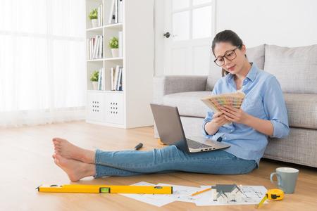 Mulher atrativa feliz que senta-se no assoalho da sala de visitas usando a casa nova do projeto móvel do portátil e guardando a ferramenta da carta da paleta que escolhe a cor.