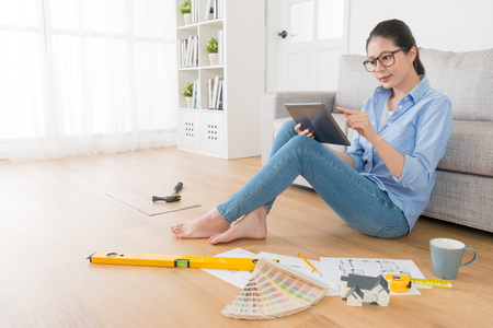 beautiful sweet female house interior designer working on wooden floor in living room at home and using mobile digital tablet computer searching design inspiration.