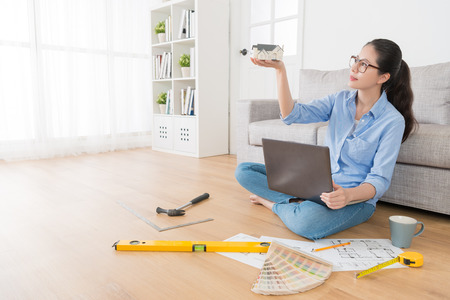 happy sweet housewife looking at home simulation model thinking how to refit house and sitting on living room floor using computer laptop design.