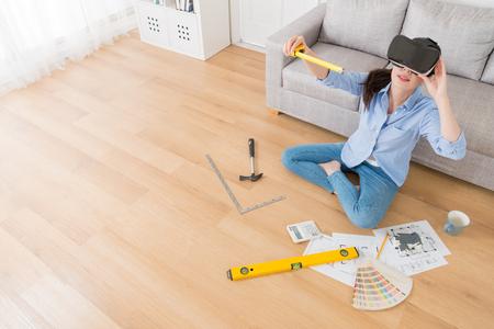 高角測定定規を用いた 3 D シミュレーション ビデオを介して仮想現実デバイス設計新しい家の若い美しさ女性エンジニアの写真を見る。