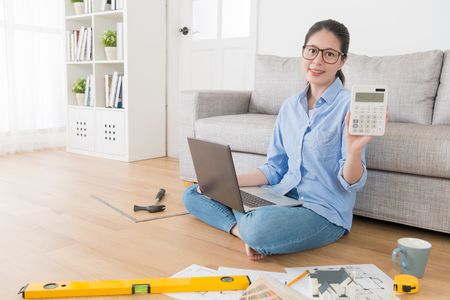 confident young housewife using computer planning house remodeling and looking at camera holding calculator showing all spent. 版權商用圖片