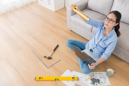 professional beauty girl designer working with computer on floor and using measuring tape simulation confirm house design format. high angle view photo.