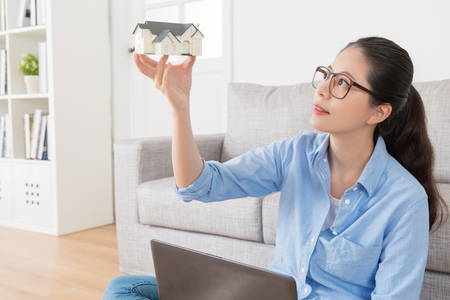 beautiful young girl showing house model thinking remodeling planning at home with computer.