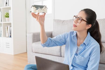 Hermosa joven que muestra la planificación modelo de planificación pensando en casa en casa con bluetooth Foto de archivo - 88081600
