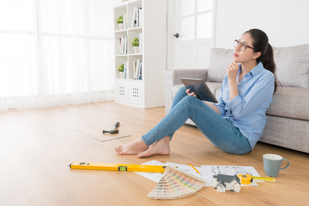 fantasize: young successful female designer holding mobile pad computer searching information and thinking house interior design with engineer tool sitting in living room wooden floor.