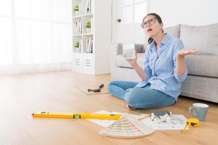 Mujer joven hermosa que sostiene la calculadora que muestra el precio del diseño de la nueva casa que siente increíble y confundido. Foto de archivo - 88081604