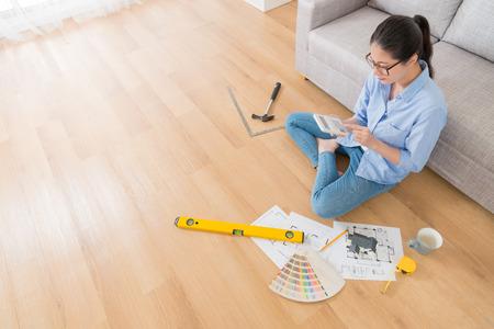 Foto de visión de ángulo alto del ingeniero elegante de la muchacha de la belleza que se sienta en piso usando la calculadora que cuenta el precio de remodelación de la casa. Foto de archivo - 88081607