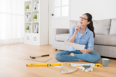 happy pretty housewife holding new house interior sketch paper daydreaming and thinking good idea making pointing gesture sitting in living room wooden floor.