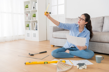 beautiful confident female house interior designer sitting in living room wooden floor and holding engineer tape ruler checking design sketch correct.