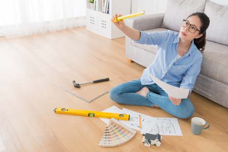 seriously pretty housewife sitting in living room wooden floor holding engineer tape ruler tool measuring house interior renew design with high angle view photo.