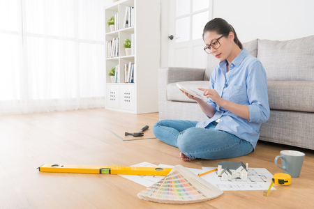 professional elegant female interior designer planning house remodeling case and using calculator counting all construction spend.