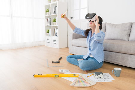 professional young woman designer wearing VR glasses looking 3D simulation video and using measuring tape checking design.