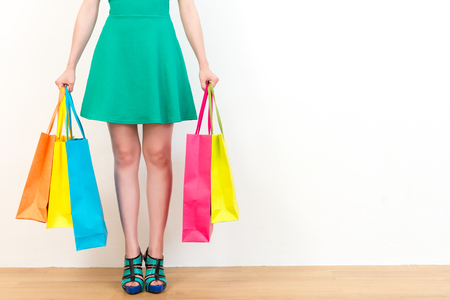comprando zapatos: beautiful green dress woman showing lot of shopping bags standing on wooden floor with white wall background empty area.