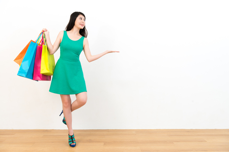 pretty smiling lady wearing green dress carrying colorful shopping bags standing on wood floor and making showing gesture displaying white empty area.