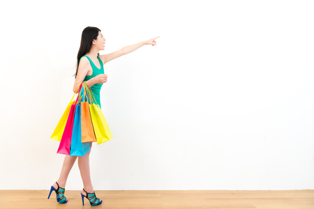 smiling young woman holding many colorful shopping bag walking on wooden floor and using hand pointing white wall background empty area. Stock Photo