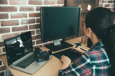전문 젊은 여성 사진의 다시보기 디자이너 사진 작가 그림을 컴퓨터에 전송 하 고 디지털 펜을 사용 하여 비즈니스 사무실 책상에 수정 손질.