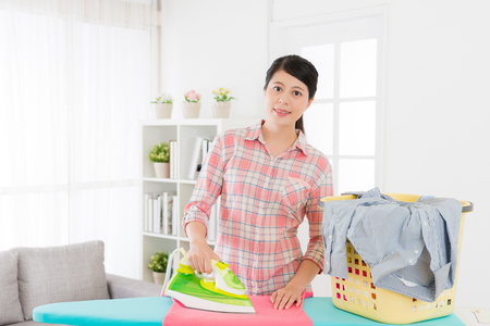 beautiful happy housewife sort out family clean clothing with iron on ironing board in living room and looking at camera smiling. Stok Fotoğraf