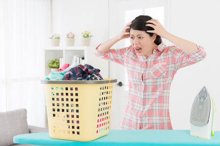 unhappy young housewife finding she having many messy family clothing must be ironing feeling collapse and looking at clothes showing shocked emotional. Reklamní fotografie