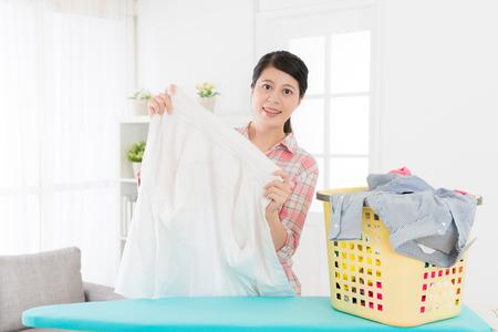 매력적인여자가 그녀가 거실에서 집에서 의류를 접을 때 깨끗하고 카메라를 찾고 흰색 셔츠를 들고 웃고.