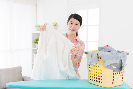 smiling attractive woman holding white shirt checking clean and looking at camera when she folding clothing at home in living room.