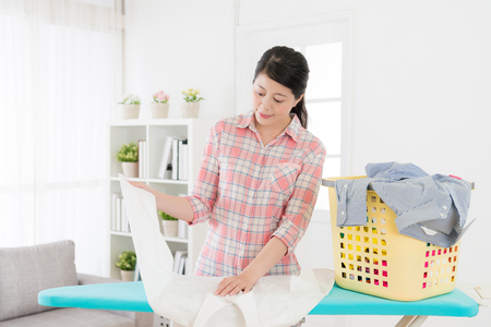 young elegant housewife using ironing board folding clothing in living room at home.