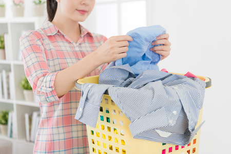 closeup photo of pretty smiling housekeeper woman inspecting clothing clean.
