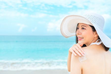 achtermeningsfoto van sexy glimlachend meisje die naar overzeese strandvakantie gaan en van de de beschermingsolie van de deklaagzoneweerstand het zonlicht uv voor de huid van het zorglichaam in de zomervakantie. Stockfoto