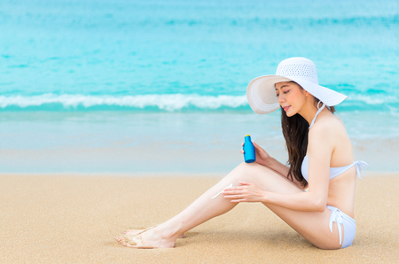 attractive happy woman using sun protection oil coating uv cream on leg resistance sunlight and wearing bikini sitting in beach at summer travel vacation.