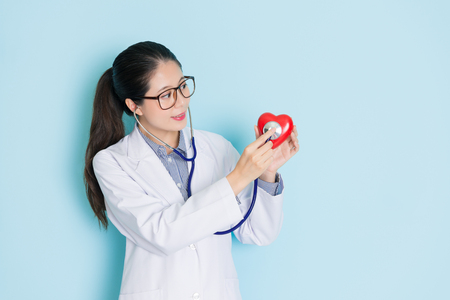 pretty attractive female doctor using stethoscope diagnostic heart in blue background showing cardiology healthy care concept.