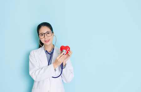 beautiful smiling female doctor looking at camera and using stethoscope touching heart showing cardiology care concept in blue background.