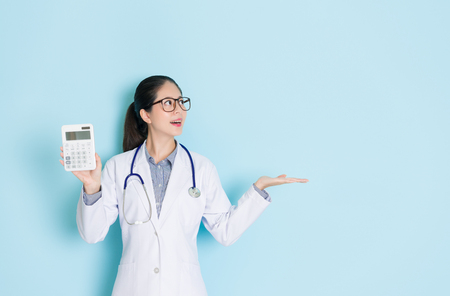 happy beautiful female doctor showing calculator and making presenting gesture displaying empty area in blue wall background. Banque d'images