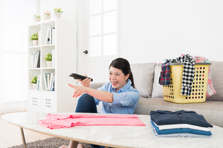 cheerful young housewife watching funny tv program relaxing in living room and pointing screen feeling happy when she folding family clothing.