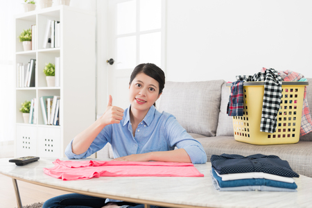 happy attractive housewife folding family clothing looking at camera smiling and showing thumb up gesture in living room when she doing housekeeping.