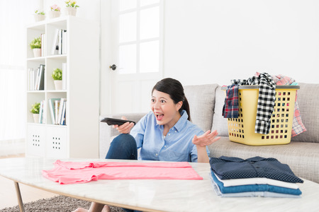 beautiful attractive woman making housekeeping folding clothing and watching television funny program relaxing in living room. Stock Photo