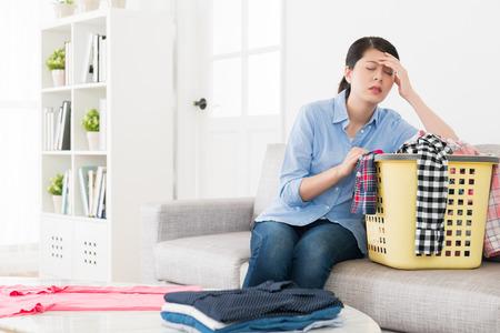 młoda elegancka gospodyni domowa czuje się zmęczona, a ból głowy boli, gdy składa odzież w salonie.