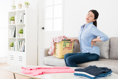 pretty young woman sitting on sofa stretching body when she folding family clothing feeling tired and getting waist painful in living room.
