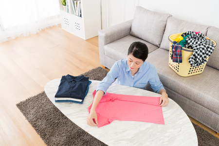 high angle view photo of pretty attractive mother folding family clothes on desk when she making household working in living room.