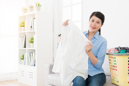 happy beautiful woman holding white clothing and looking at camera smiling in living room at home when she doing housekeeping. Reklamní fotografie