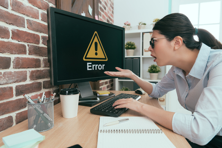 sadness suit woman sitting on working desk using keyboard typing making report but computer showing error information let her feeling dumbfounded. Stock Photo