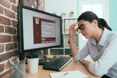 pretty attractive office worker lady thinking work solution when her company working computer getting blackmail virus invasion.