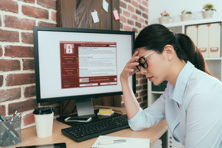 sadness company agent woman finding working computer getting blackmail virus attack thinking solution at office desk and feeling depression.