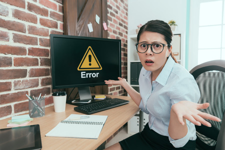 young agent woman looking at camera and showing confused posing when her office computer getting problem showing error information.