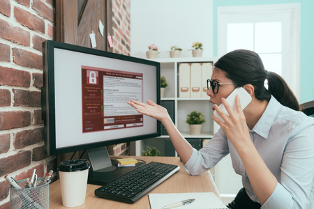 professional business woman using mobile smart phone calling for help when her company working computer getting virus invasion.