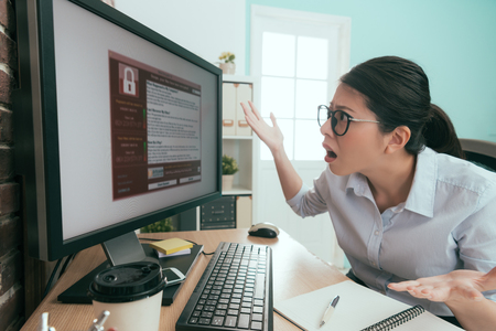 puzzled unhappy business manager looking at computer screen showing extort virus information and making confusion posing feeling shocked.
