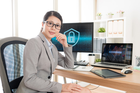 confidence young female business worker sitting in workplace office looking at camera smiling when she doing online cyber security work.