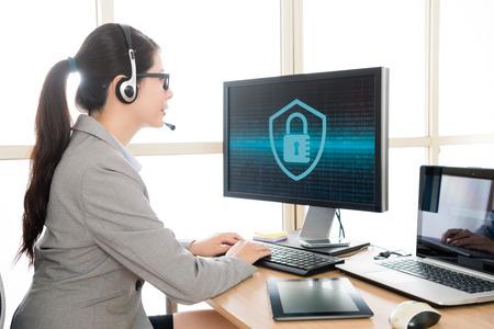 Professioneller hübscher weiblicher Büroangestellter, der das Tragen des Kopfhörers mit Kunden trägt und Daten in on-line-System eingibt, um Cybersicherheitsproblem zu lösen. Standard-Bild