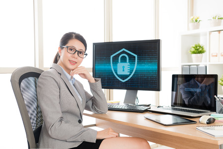 happy beautiful female office worker looking at camera when she processing online cyber security system problem in office.